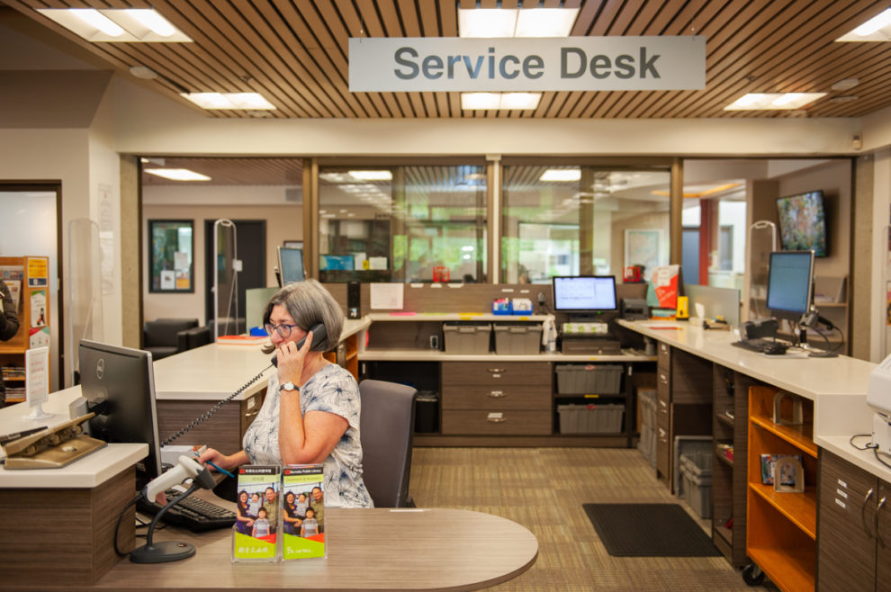 Staff on phone behind the Service Desk at Cameron Branch