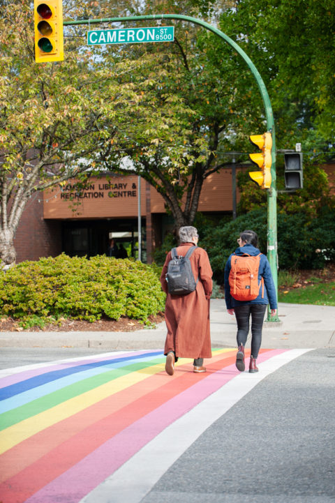 Two people walking across the rainbow crosswalk outside the Cameron Branch entrance